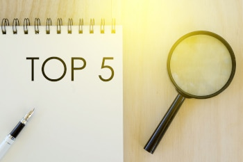 Top view of pen,magnifying glass and notebook written with Top 5 on wooden background.